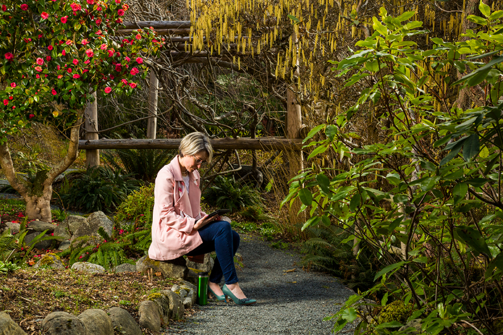Woman sitting in Japanese Garden looking at a tablet.